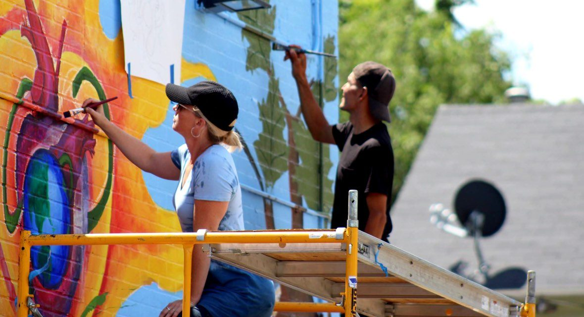 Volunteers painting the side of a building